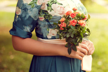woman holding a bouquet of summer in the Park, floral dress, with a focus on flowers. Summer mood, holidays