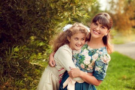 Schöne junge Mutter in einem geblümten Kleid und Tochter Teenager 10 Jahren im Sommer im Park umarmen, gute Familienbeziehungen Standard-Bild - 66915752