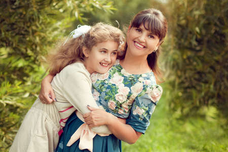 Beautiful young mother in a floral dress and daughter teen 10 years hugging in the Park in the summer, good family relationships