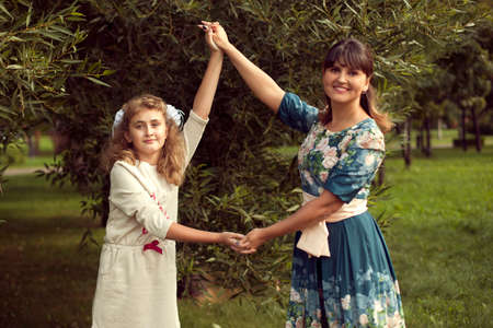 Teen girl plays with mom's hands in the summer on the nature, relax on weekends, holidays, entertainment