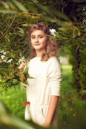 beautiful teenage girl 10 years old with long blonde hair stands in the summer with greenery and proudly looks at the camera, fashionable posing