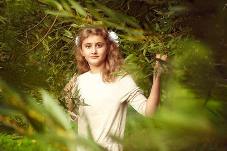 Schöne Teenager-Mädchen 10 Jahre mit langen blonden Haaren steht im Sommer mit viel Grün und blickt stolz in die Kamera, modisch posiert Standard-Bild - 66915766