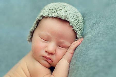 Neugeborenes Baby in der fötalen Position auf einem blauen Hintergrund in einer Strickmütze schlafen, Gesicht Nahaufnahme Standard-Bild - 66915818