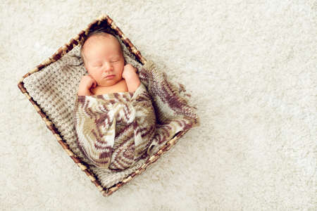 A newborn baby sleeps in a drawer wrapped in a knitted brown scarf on the white carpet, the child warm and cozy in bright bedroom