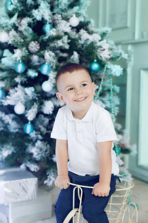 Fun boy 3 years old playing in the room decorated for the Christmas tree. Beautiful Christmas interior in white and blue colours, happy kid waiting for presents