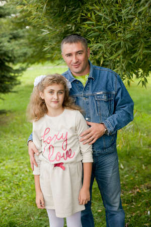 Father hugs daughter teen summer outdoors, happy family resting in the Park. The concept of traditional family values Standard-Bild