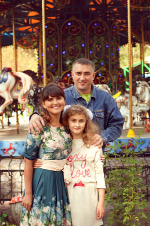 A normal happy family posing in the Park mom, dad and daughter 10 years fun walk in the summer Park
