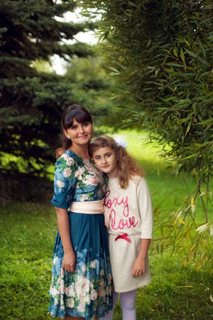 Happy family on a walk in the Park in the open air, mother and daughter 10 years hugging on green summer background