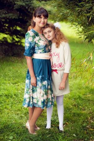 Glückliche Familie auf einem Spaziergang im Park an der frischen Luft, Mutter und Tochter 10 Jahre auf grünen Sommer Hintergrund umarmt Standard-Bild - 66916518