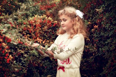 Schöne blonde Mädchen im Sommer kümmert sich um Berberitze Sträucher, die Person in Einheit mit der Natur, für Pflanzen Pflege Standard-Bild - 66916721