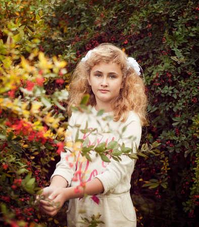 Schöne blonde Mädchen im Sommer kümmert sich um Berberitze Sträucher, die Person in Einheit mit der Natur, für Pflanzen Pflege Standard-Bild - 66916726