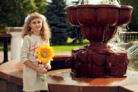 Beautiful 10 years old girl standing near a fountain, holding a sunflower walking around the city Standard-Bild