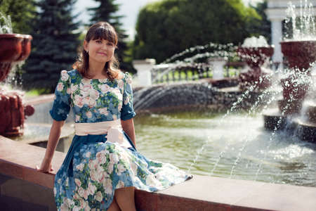 warmth: beautiful woman-brunette in floral dress sitting near the fountain in the Park and enjoy the summer warmth, a walk in the city in Russia Stock Photo