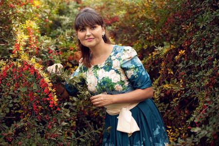 Schöne glücklich gleichaltrige Frau im Park an einem warmen Sommertag, geht ein Mädchen in einem geblümten Kleid im Freien Standard-Bild - 66916816