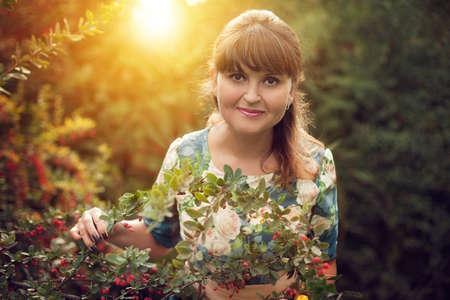 Schöne glücklich gleichaltrige Frau im Park an einem warmen Sommertag, geht ein Mädchen in einem geblümten Kleid im Freien Standard-Bild - 66916818