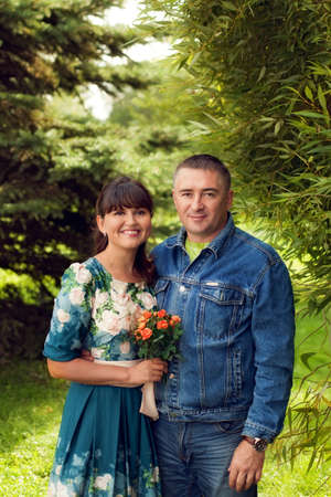 Beautiful couple, middle-aged man and a young wife in a floral dress standing together in the summer outdoors, family walk in the Park
