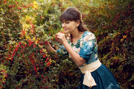 beautiful happy brunette woman in the park on a warm summer day, a girl in a floral dress walks outdoors