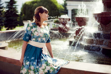 beautiful woman-brunette in floral dress sitting near the fountain in the Park and enjoy the summer warmth, a walk in the city in Russia Standard-Bild