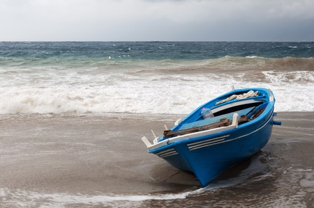 the boat in danger of being dragged off by the sea  photo
