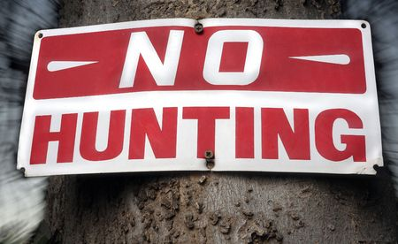 Distressed no hunting sign. Background blurred with flash drag.