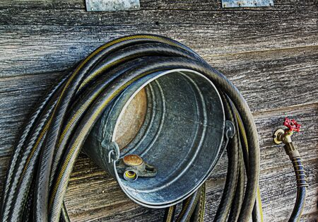DIY bucket hose hanger. Grunge style. Stock Photo