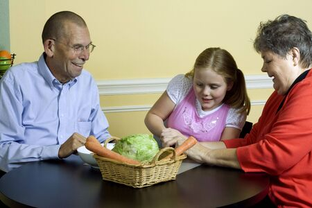 Young girl with grandparents cutting vegetables at the dining table.