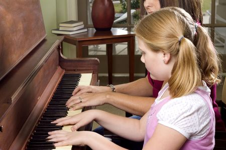 teaching music: Young Girl Taking Piano Lessons Stock Photo
