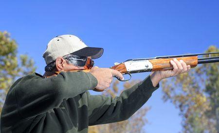 hombre disparando: Hombre disparando una escopeta.  Foto de archivo
