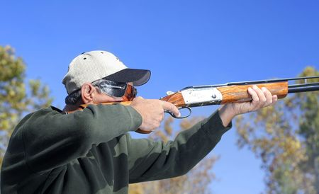 Man shooting a shotgun.