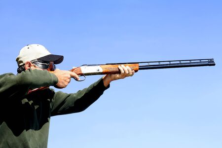 사격: Man shooting skeet.