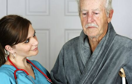Nurse helping a senior man on crutches - horizontal Stock Photo