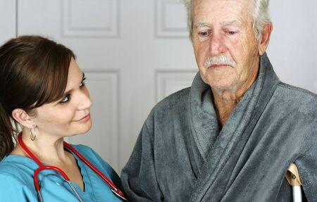 Nurse helping a senior man on crutches - horizontal Stock Photo