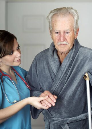 Nurse helping a senior man on crutches - vertical