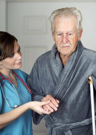 Nurse helping a senior man on crutches - vertical
