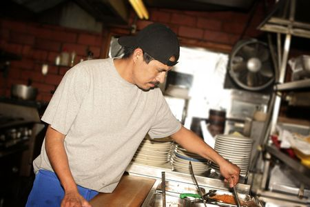 Hispanic kitchen staff. Grid spot used on flash to place emphasis on subject