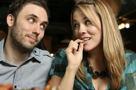 Close up of a young couple dining at a restaurant. Woman eating shrimp. Shallow dof with background and foreground blurred
