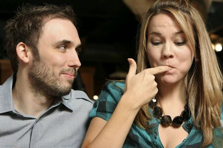 young couple dining at a  restaurant. Woman licking fingers. Shallow dof with background blurred Stock Photo