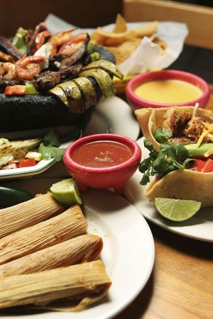 Vertical shot of a variety of Mexican dishes. Shallow dof with central portion of image in focus.