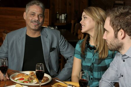 Three people dining at a Mexican restaurant. Focus on mature male.
