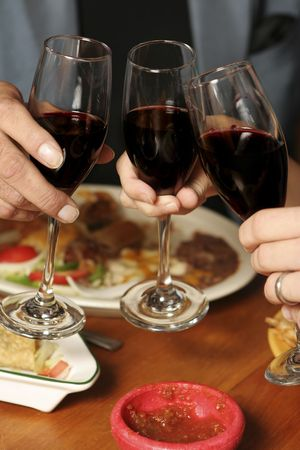 Three people toasting at a Mexican restaurant. Shallow dof. Foregroundbackground blurred. Focus on glasses. Stock Photo