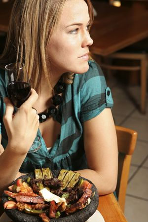 Young woman with wine gazing out of a restaurant window. Stock Photo