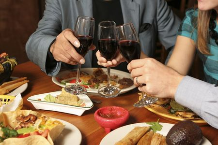 Horizontal shot of three people toasting at a Mexican restaurant. Foregroundbackground blurred. Focus on glasses.
