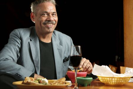 Smiling man dining in a Mexican restaurant.