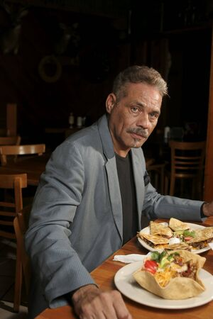 Mature man dining in a Mexican restaurant.