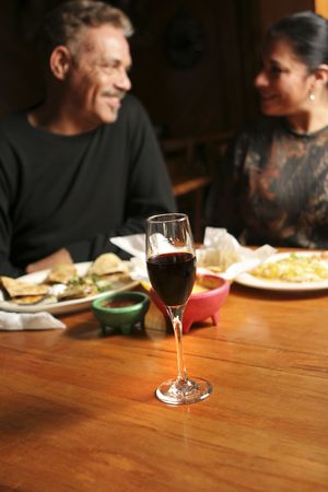 Mature couple dining out. Shallow dof with focus on wine glass. Couple and background blurred.