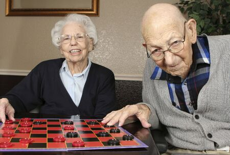 Active senior couple playing checkers.