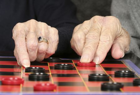 Close up of senior adult hands and checkers