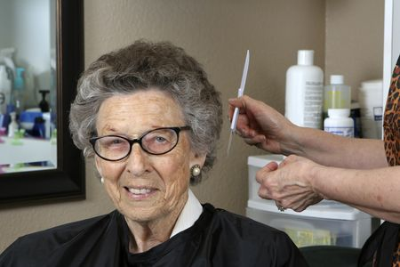 grooming: Active Senior woman at the hair salon with comb