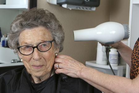 Actieve senior vrouw in de kap salon met föhn