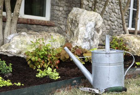 Watering can and trowel nest to landscape. Shallow depth of field.